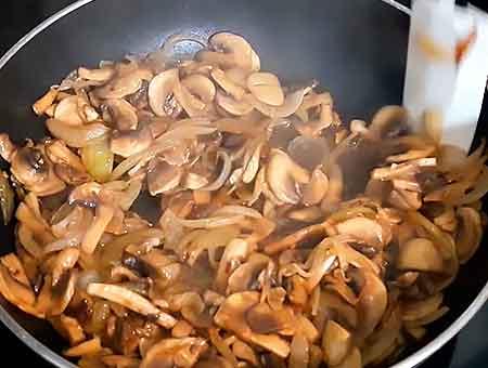 Перемешиваем лук с грибами, продолжаем обжаривать