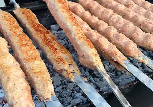 шампуры с кебаб лежат на мангале